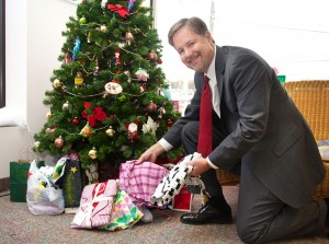Don Anderson, owner of the Cruise Store in East Longmeadow, places pajamas under the tree at his store.  Additional Pajama Project collection locations include the St. Francis Chapel in Springfield and Tower Square's City Walk Café on Wednesdays in December from 12pm-1:30pm.